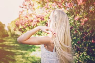 Woman with  long blond hair in the garden with flowers. Beautiful girl on a sunny day.