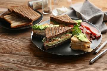 Plate with delicious sandwiches on wooden table