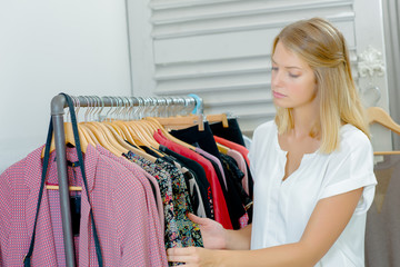 Lady browsing through rail of clothes