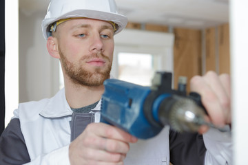 young man using power drill on wall