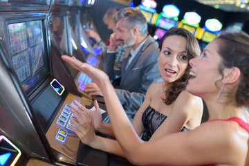 beautiful women in dress playing slot machine
