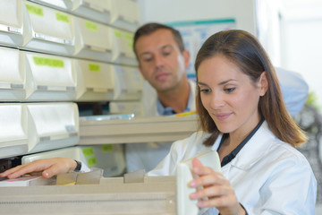 Pharmacists looking in drawers
