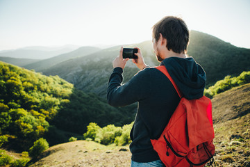Man taking a photo of the mountains with smartphone.