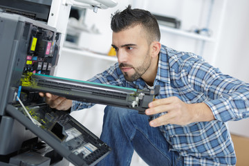 young male technician repairing digital photocopier machine