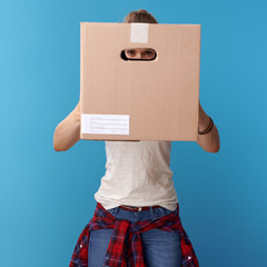 active hipster looking through cardboard box on blue