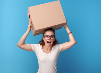 shocked active woman with cardboard box on head on blue