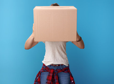 young hipster holding cardboard box in front of face on blue