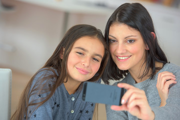 cute child and mother make selfie on new mobile phone