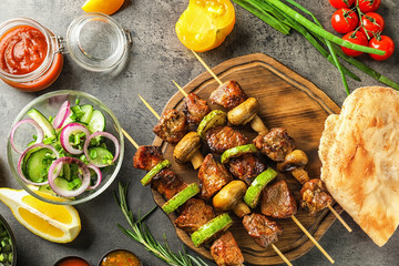 Barbecue skewers with juicy meat and vegetables on wooden board
