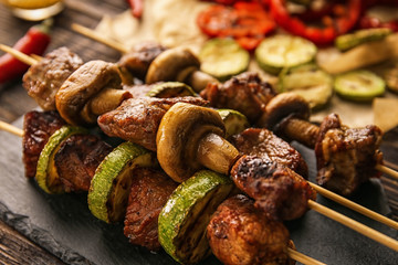 Barbecue skewers with juicy meat and vegetables on slate plate