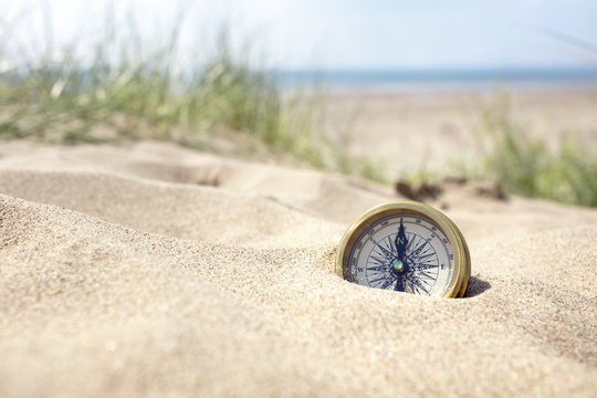 Compass on the beach with sand and sea