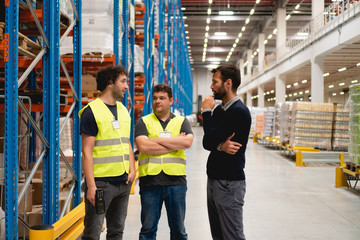 Manager talking with employees in warehouse