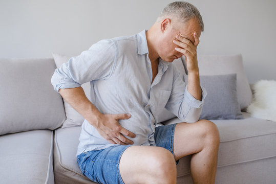 A middle-aged man has a stomach ache