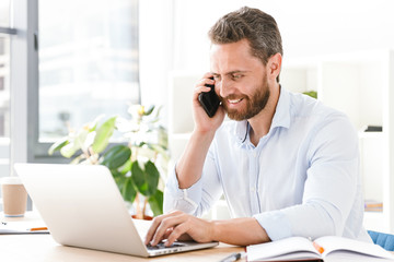Handsome bearded man talking by mobile phone using laptop computer.