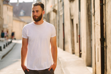 Hipster handsome male model with beard wearing white blank t-shirt with space for your logo or design in casual urban style Wall mural