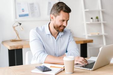 Happy bearded man sitting in office working