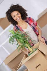 beautiful woman with carton boxes moving in her new house