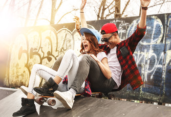 Young teen couple sitting on ramp and hangout at the skate park .Laughing and fun.
