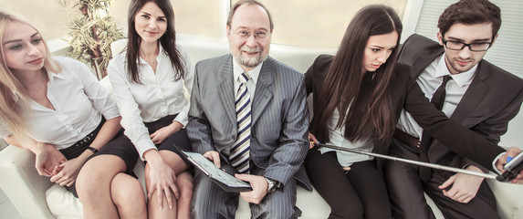 beautiful young woman employee makes a selfie with his boss and business team sitting near the window in the office.