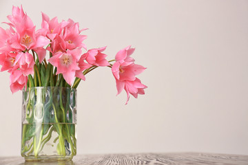 Vase with beautiful tulips on wooden table against light background