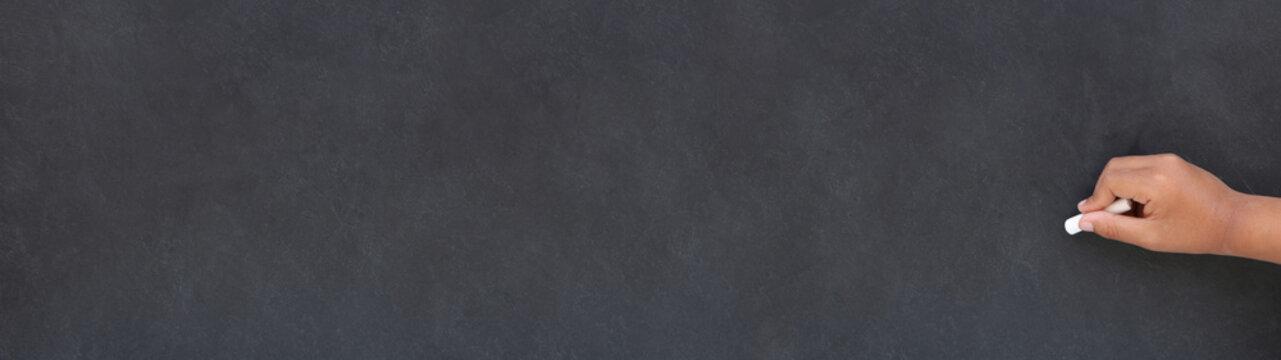 Main d'enfant écrivant à la craie sur un tableau