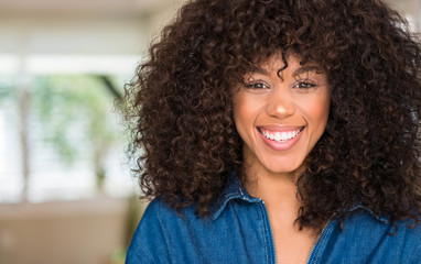 African american woman with a happy face standing and smiling with a confident smile showing teeth