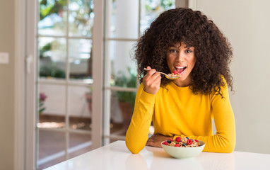 African american woman eating cereals, raspberries and blueberries with a confident expression on smart face thinking serious
