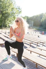 Picture of sports woman exercising among benches in summer day
