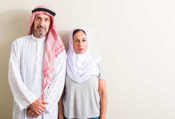 Middle age arabic couple, woman and man with a confident expression on smart face thinking serious