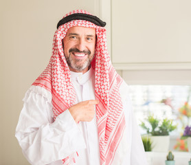Middle age arabian man at home with surprise face pointing finger to himself