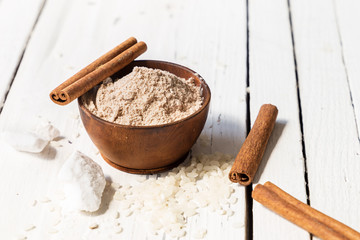 Homemade face scrub and body from rice, cinnamon and soda in a wooden bowl on a white wooden table