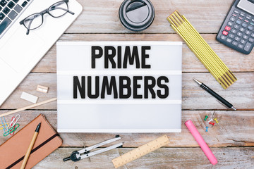 Text Prime Numbers in light box on office desk flat lay