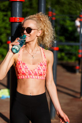 Photo of sports woman wearing sunglasses with bottle of water near horizontal bar in park
