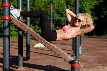 Photo of sports woman wearing sunglasses training press in park
