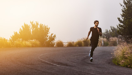 Athlete running on mountain road Wall mural