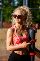Photo of sports woman wearing sunglasses holding phone in hands of park