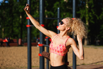 Photo of smiling sports woman wearing sunglasses doing selfie in park