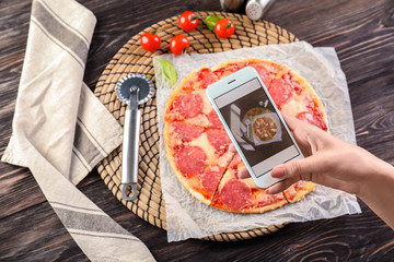Woman photographing pepperoni pizza with mobile phone