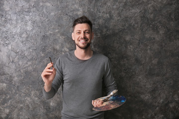 Male artist with paint tools and palette on grey background
