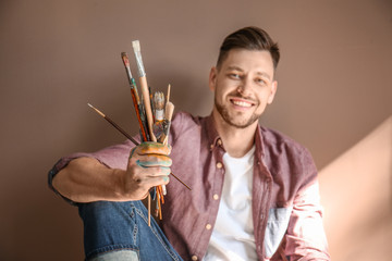 Male artist with paint tools on color background