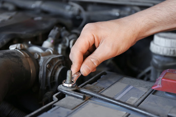 Male mechanic fixing car in service center, closeup