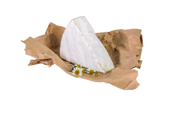 Piece of brie on wrapping paper with chamomile isolated on white