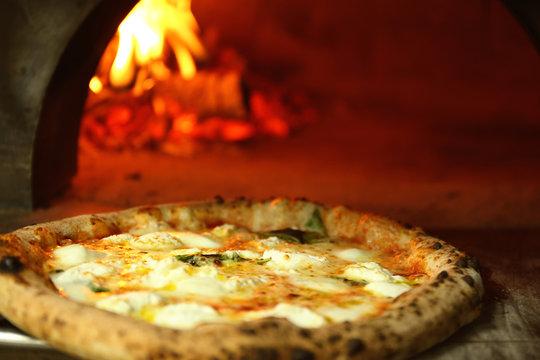 Tasty pizza near firewood oven in kitchen
