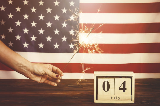 Retro toned cropped shot, woman holding burning sparkler, bengal light on American flag background. 4th of July, USA Independence day date on wooden cube calendar. Vintage filter, copy space, close up
