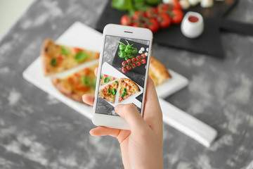 Woman photographing delicious pizza Margherita with mobile phone