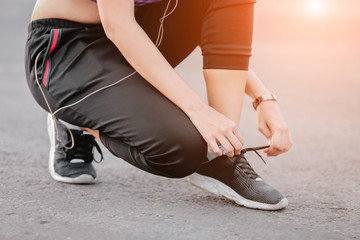 Young woman runner tying shoelaces with copy space  healthy lifestyle and sport concepts.