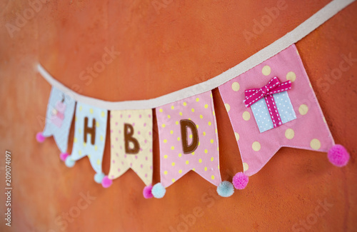 Colorful Fabric Birthday Party Flag Hanging On Orange Cement Wall