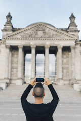 man taking a picture of the Reichstag, in Berlin.