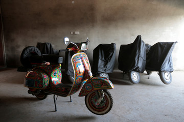 A restored Vespa scooter, painted in Pakistani truck art style, is parked beside covered scooters at a Vespa restoration and repair workshop in Islamabad