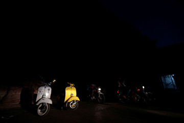 Vespa scooters are seen at night in Lahore
